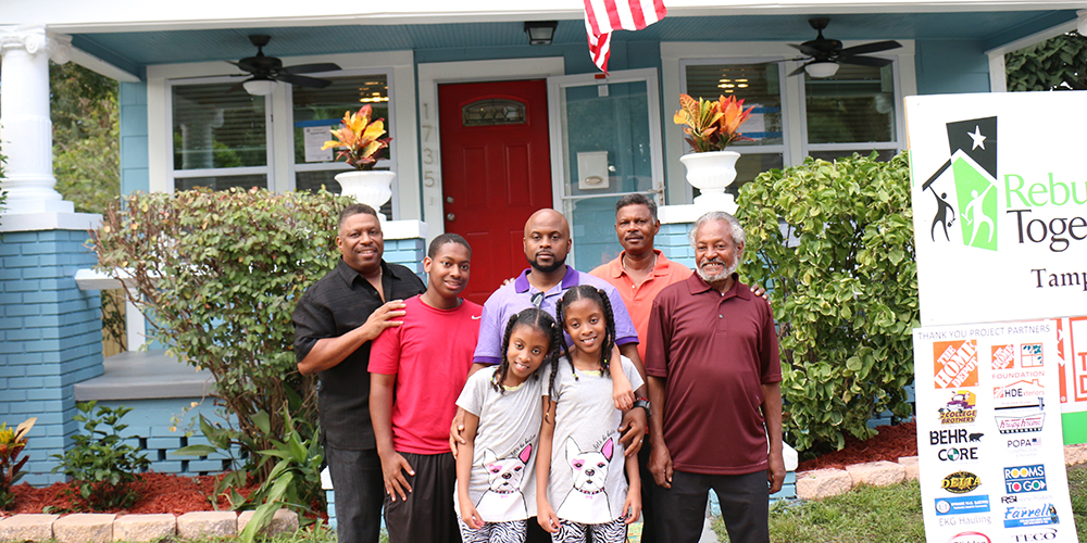 Cruse family outside newly repaired home