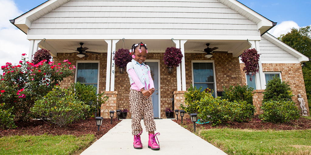 Young girl poses outside new Habitat for Humanity home