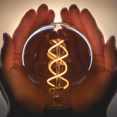 Feit glass bulb with curved filament held in hand