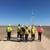 Group walking towards wind turbines in Texas