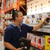 Home Depot associate looks at smart thermostats in-ailse