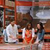 Home Depot associate and customer look at Pergo flooring