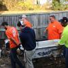 Volunteers move old bathtub through yard