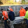Volunteers move old bathtub through yard